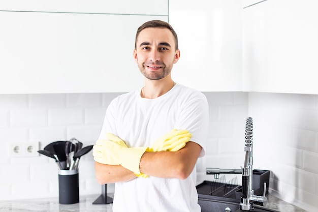 Young man in gloves on the kitchen at home