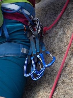 若い男は彼のハーネスのクイックドローをぶら下げて岩に登りに行きます