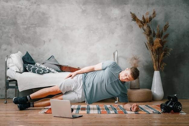 若い男は自宅でスポーツに行き、オンラインでトレーニングします。アスリートは板を横に置き、寝室のラップトップで時間を見て、背景にはベッド、花瓶、カーペットを置きます。