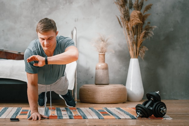 젊은 남자가 집에서 스포츠를 위해 온라인으로 훈련합니다. 운동 선수는 판자를 만들고, 스포츠 시계, 침실의 스톱워치, 배경에는 침대, 꽃병, 카펫에서 시간을 봅니다.