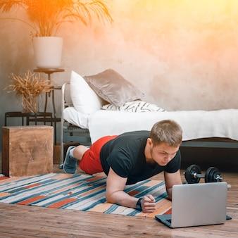 若い男は自宅でスポーツに行き、オンラインでトレーニングします。アスリートは板を作り、映画を見て、寝室のラップトップから勉強します。背景にはベッド、花瓶、カーペットがあります。