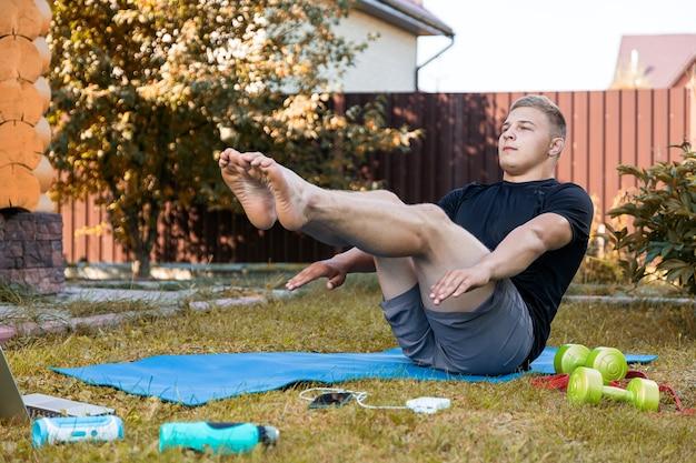 若い男は自宅でスポーツに行き、オンラインでトレーニングします。アスリートはプレスをし、笑顔で、夏の日の裏庭に開いているラップトップ、電話、ダンベルがあります。