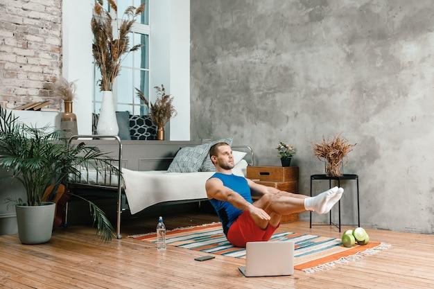 若い男は自宅でスポーツに行き、オンラインでトレーニングします