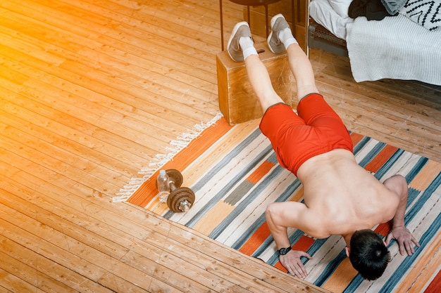 The young man goes in for sports at home. sportsman with blac hair does push-ups on carpet in bedroom, top view
