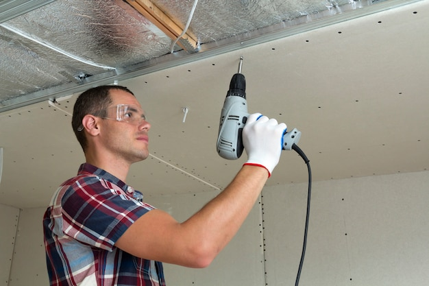 Young man in goggles fixing drywall suspended ceiling to metal frame using electrical screwdriver on ceiling insulated with shiny aluminum foil. renovation, construction, do it yourself concept.