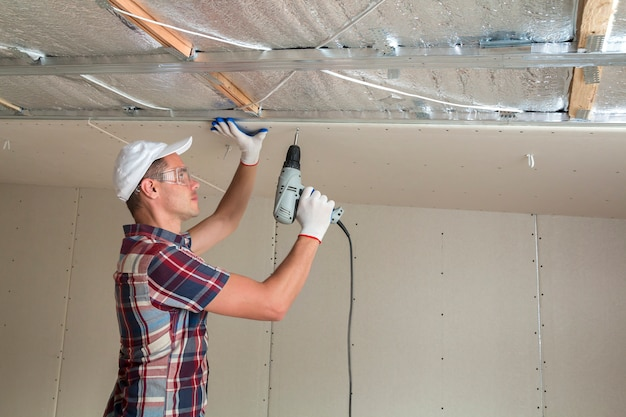 Young man in goggles fixing drywall suspended ceiling to metal frame using electrical screwdriver on ceiling insulated with shiny aluminum foil.