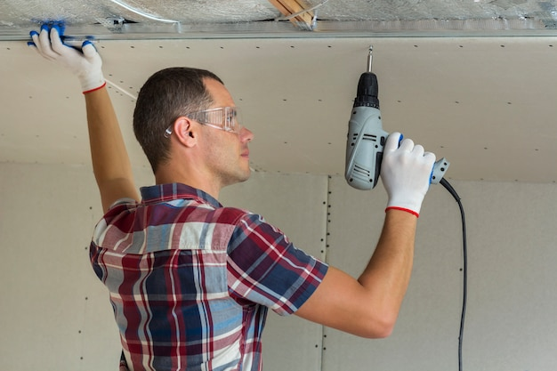 Young man in goggles fixing drywall suspended ceiling to metal frame using electrical screwdriver on ceiling.