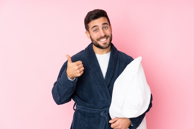 Young man going to sleep on pink wall giving a thumbs up gesture