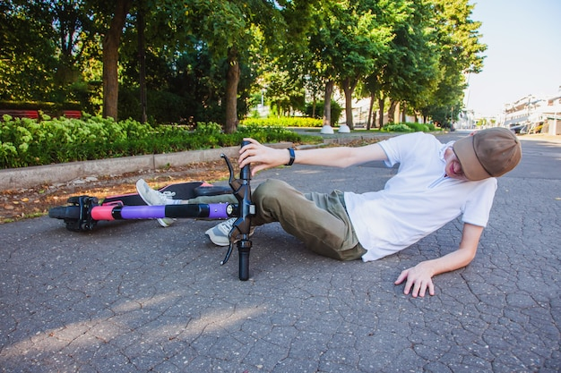 A young man got into an accident on an electronic scooter, lies on the asphalt and screams in pain.