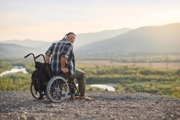 若い男は日の出の山の頂上で車椅子から彼の足に立ち上がった。病人は癒されました。