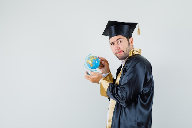 Young man in graduate uniform choosing destination on school globe and looking indecisive .