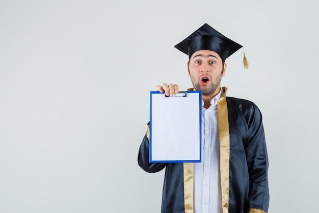 Giovane uomo in uniforme laureato che tiene appunti e guardando stupito, vista frontale.