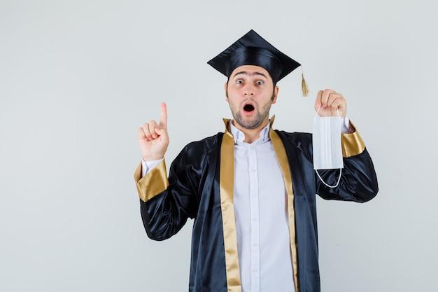 Giovane uomo laureato in uniforme che tiene mascherina medica, rivolto verso l'alto e guardando sorpreso, vista frontale.