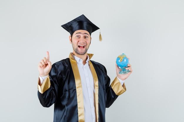 Giovane uomo laureato in uniforme che tiene il globo della scuola, rivolto verso l'alto e guardando allegro, vista frontale.