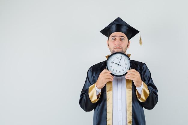Giovane uomo in uniforme laureato tenendo l'orologio da parete e guardando agitato, vista frontale.