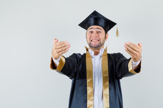 Giovane uomo in uniforme laureato che invita a venire e che sembra allegro, vista frontale.