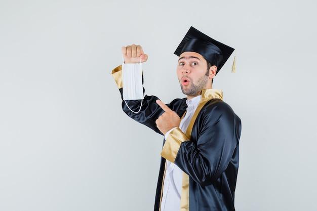 Giovane uomo in uniforme laureato che punta alla mascherina medica e che sembra sorpreso.