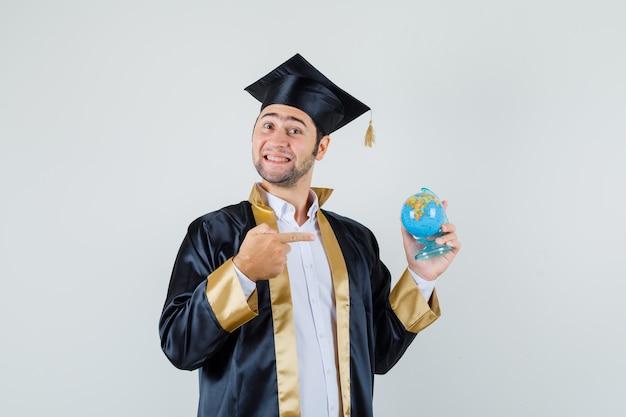 Giovane uomo in uniforme laureato che punta al globo della scuola e guardando allegro, vista frontale.