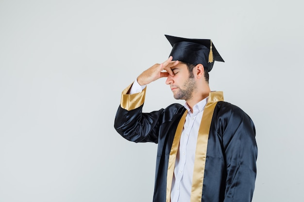 Young man in graduate uniform rubbing eyes and nose and looking tired , front view.