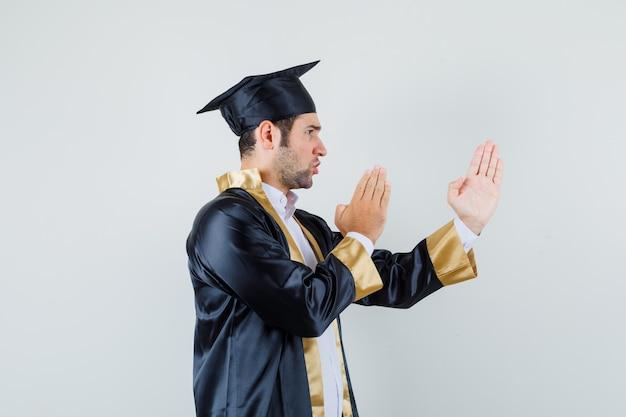 Giovane in uniforme laureato che mostra il gesto di taglio di karate e che sembra dispettoso.