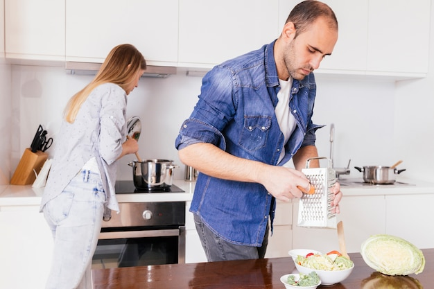 백그라운드에서 음식을 준비하는 그의 아내와 당근 격자 젊은 남자