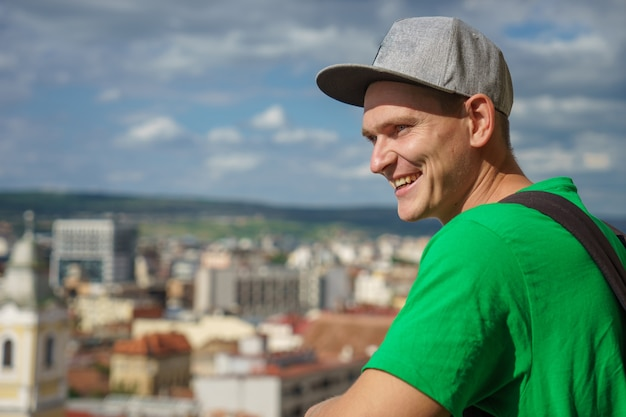 Young man in a gray baseball cap and green t-shirt on background of the city and blue sky with clouds.