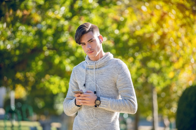 Young man in gray sweater in the park with mobile phone and headphones