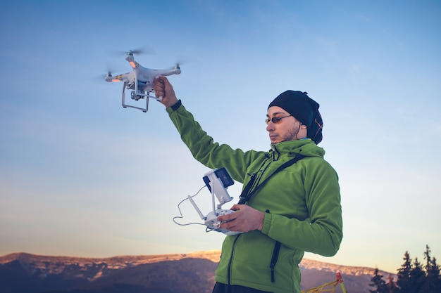 Young man in green jacket holding a drone and remote controller ski resort in the background winter