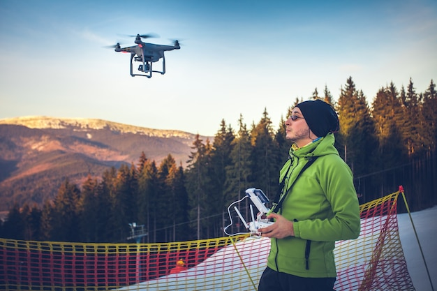 Young man in green jacket operating a drone using a remote controller ski resort in the background
