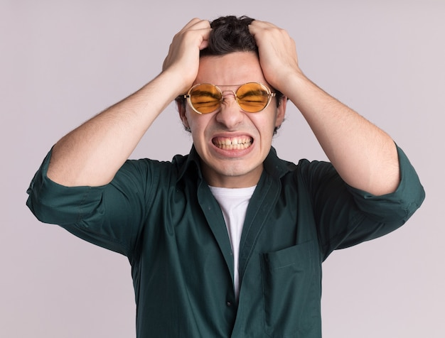 Young man in green shirt wearing glasses going wild pulling his hair standing over white wall