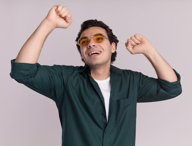 Young man in green shirt wearing glasses happy and excited raising fists celebrating victory standing over white wall
