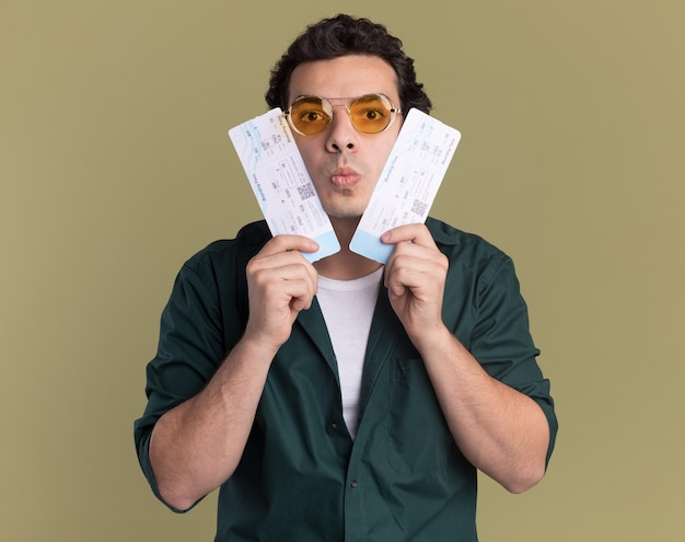 Young man in green shirt wearing glasses holding air tickets looking at front confused standing over green wall