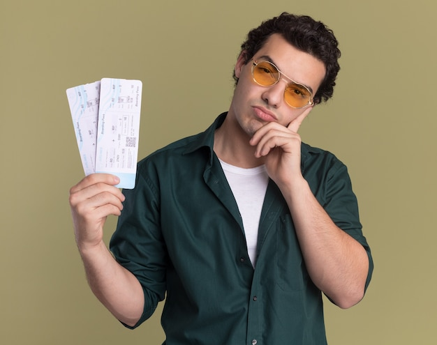 Young man in green shirt wearing glasses holding air tickets looking at front puzzled thinking standing over green wall