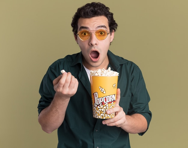 Young man in green shirt wearing glasses holding bucket with popcorn looking at front amazed and surprised standing over green wall