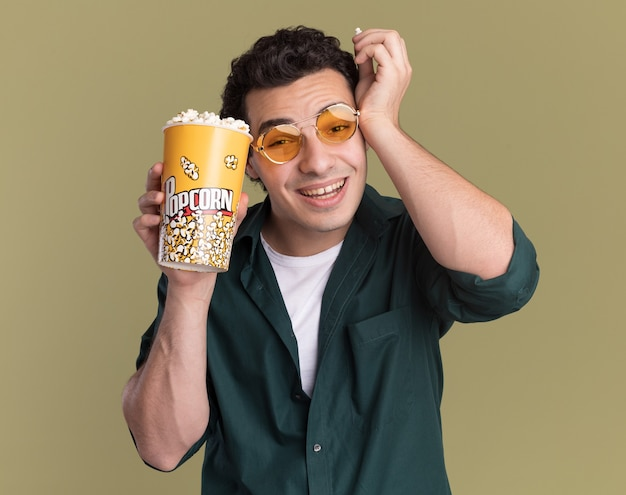 Giovane uomo in camicia verde con gli occhiali tenendo la benna con popcorn guardando davanti sorridente felice e allegro in piedi sopra la parete verde