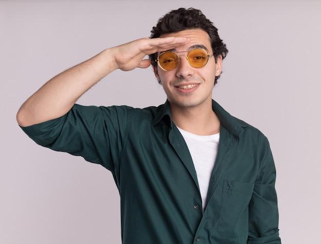 Giovane uomo in camicia verde con gli occhiali che guarda lontano con la mano sopra la testa in piedi sul muro bianco