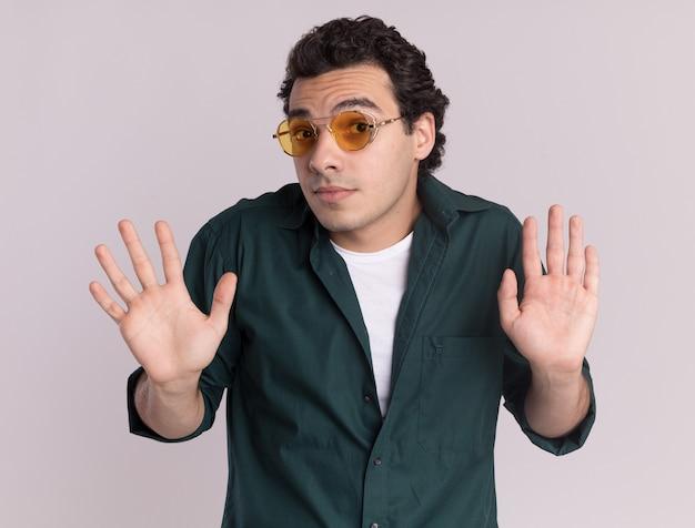 Giovane uomo in camicia verde con gli occhiali guardando davanti confuso scrollare le spalle non avendo risposta in piedi sopra il muro bianco