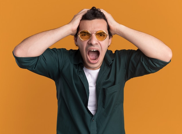 Young man in green shirt wearing glasses looking at front crazy mad and angry pulling his hair standing over orange wall