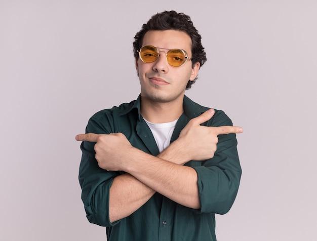 Giovane uomo in camicia verde con gli occhiali guardando davanti sorridendo fiducioso attraversando le mani che puntano con il dito indice ai lati in piedi sopra il muro bianco