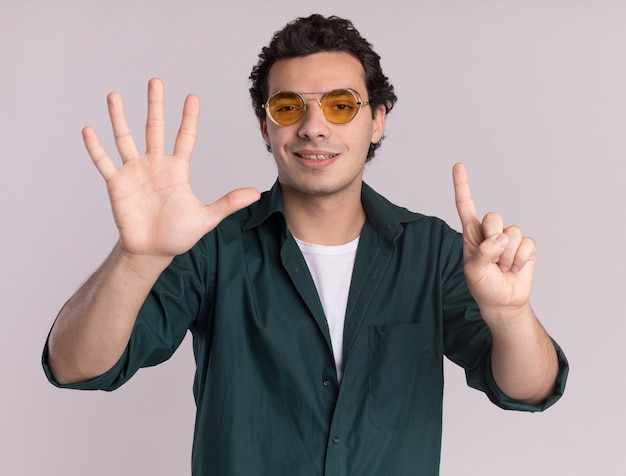 Giovane uomo in camicia verde con gli occhiali guardando davanti sorridente fiducioso che mostra il numero sei in piedi sul muro bianco