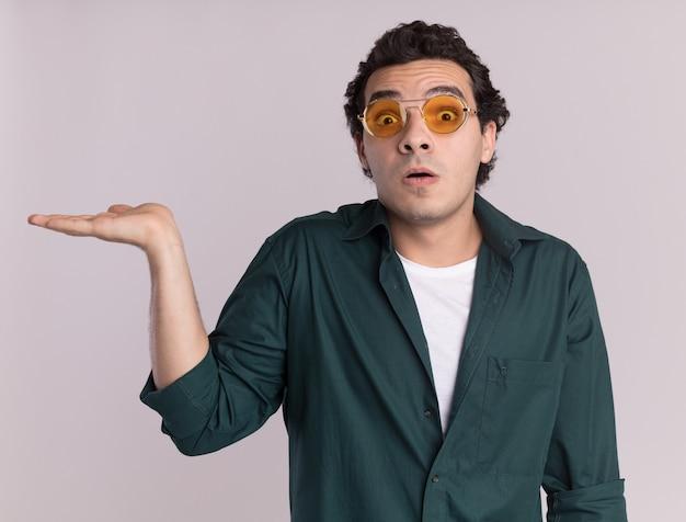 Giovane uomo in camicia verde con gli occhiali guardando davanti sorpreso presentando lo spazio della copia con il braccio della mano in piedi sul muro bianco