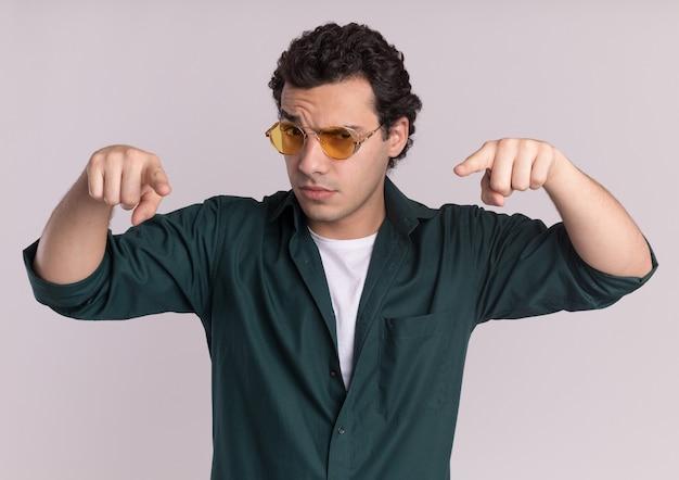 Giovane uomo in camicia verde con gli occhiali guardando davanti con espressione fiduciosa che punta con il dito indice verso il basso in piedi sul muro bianco