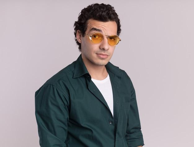 Giovane uomo in camicia verde con gli occhiali guardando davanti con espressione scettica in piedi sopra il muro bianco