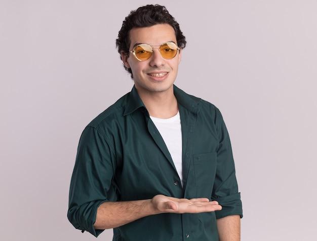 Giovane uomo in camicia verde con gli occhiali guardando la parte anteriore con il sorriso sul viso che presenta qualcosa con il braccio della mano in piedi sul muro bianco