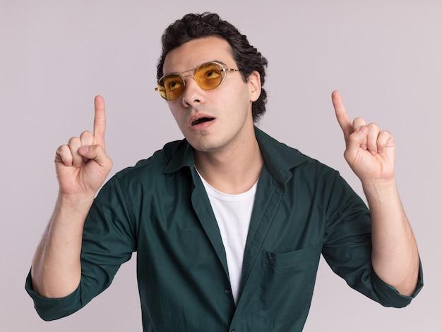 Giovane uomo in camicia verde con gli occhiali alzando lo sguardo perplesso indicando con le dita indice in piedi sopra il muro bianco