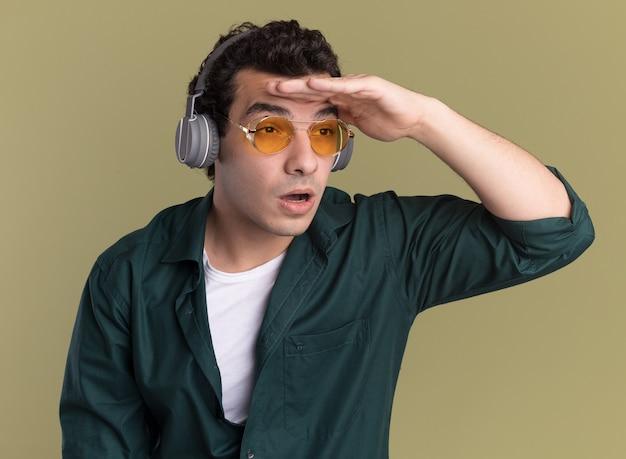 Giovane uomo in camicia verde con gli occhiali con le cuffie che guarda lontano lontano con la mano sopra la testa in piedi sul muro verde