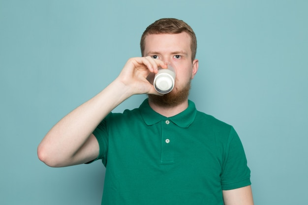 Young man in green t-shirt drinking glass with milk