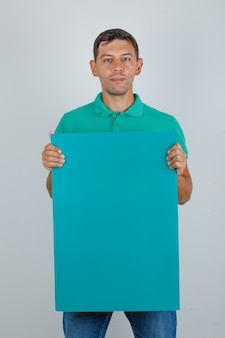 Young man in green t-shirt holding blue poster, front view.