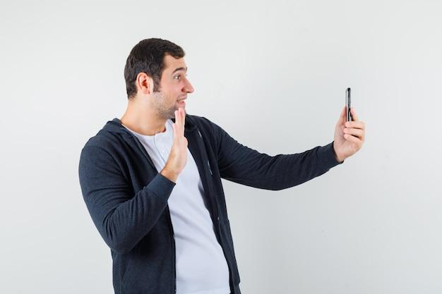 흰색 티셔츠와 지퍼 앞 검은 까마귀에 videocall을 통해 누군가를 인사하고 행복, 정면보기를 찾는 젊은 남자.