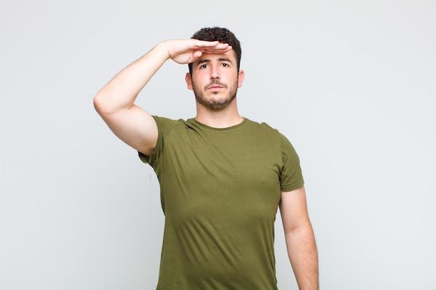 Молодой человек приветствует камеру военным салютом в знак чести и патриотизма, проявляя уважение